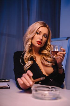 femme séduisante assise avec un cigare et un verre de whisky au bureau Banque d'images