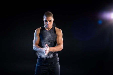 handsome african american sportsman clapping hands with talc on black Stock Photo