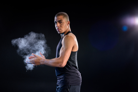 african american sportsman clapping hands with talc on black Stock Photo