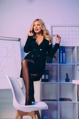 sexy woman putting leg on chair and talking by smartphone Banque d'images