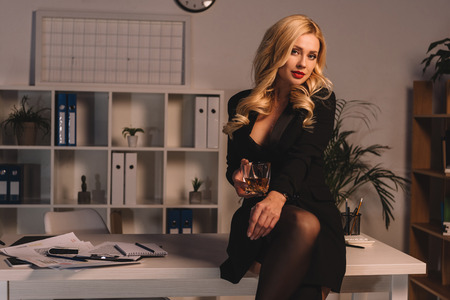 sexy businesswoman posing with glass of whiskey at office in evening and looking at camera