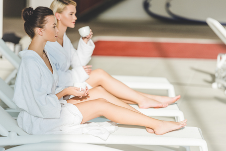 attractive young women drinking coffee at spa center while sitting on sunbeds Stock Photo