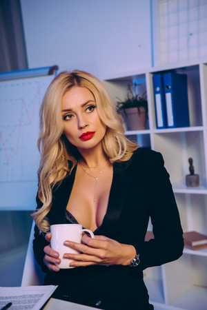 seductive blonde woman holding cup of coffee
