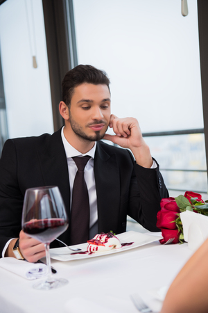 partial view of man in suit sitting at table on romantic date with girlfriend in restaurant, st valentine day