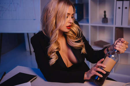 attractive sexy blonde woman opening bottle of whiskey