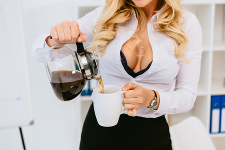 cropped image of seductive woman pouring coffee in cup Stock Photo