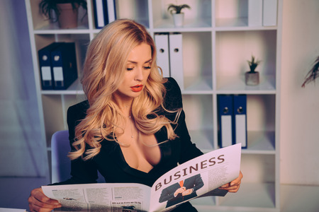 seductive businesswoman reading business newspaper in office