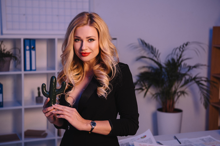 smiling sexy woman holding artificial cactus in office and looking at camera Фото со стока