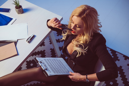 overhead view of sexy woman reading working contract in office Stock Photo