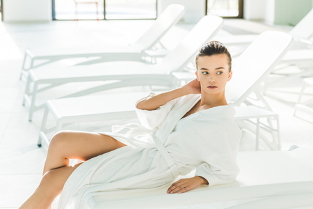 attractive young woman in bathrobe relaxing on sunbed at spa Фото со стока