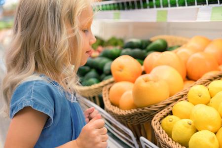 adorable little kid choosing lemons and oranges in supermarket Foto de archivo - 104563604