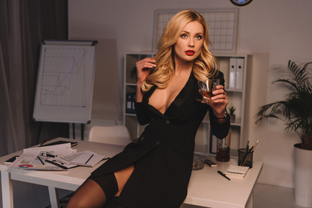 donna in posa con un bicchiere di whisky in ufficio in serata e distogliere lo sguardo