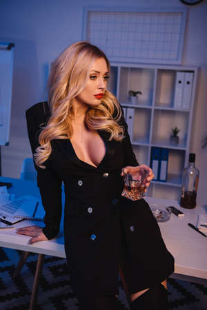 seductive woman holding glass of whiskey in office