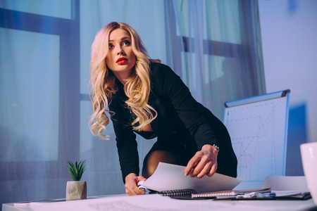 sexy businesswoman with knee on table stapling papers with stapler and looking away 写真素材