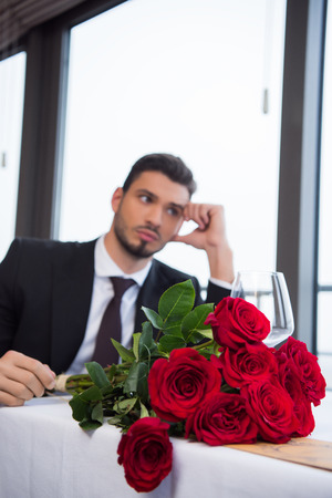 selective focus of man in suit with bouquet of red roses waiting for girlfriend in restaurant 写真素材