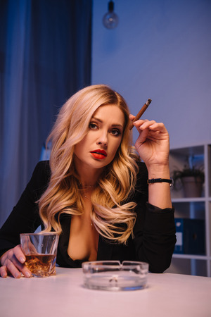 seductive woman sitting with cigar and glass of whiskey in office and looking at camera Zdjęcie Seryjne