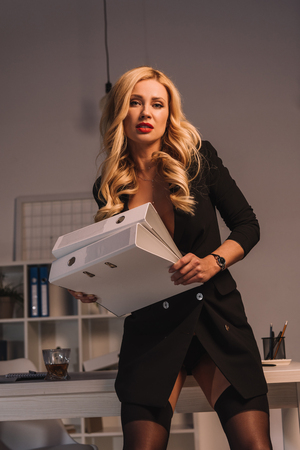 seductive woman standing with folders in office