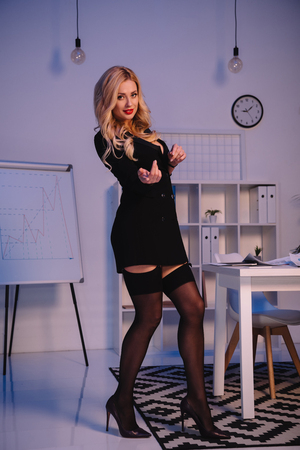 seductive woman in jacket and stockings showing coming gesture