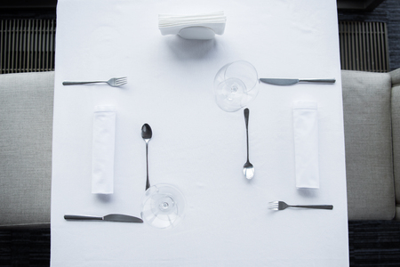 top view of arranged cutlery and wineglasses on table with white tablecloth in restaurant
