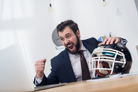 excited businessman with rugby helmet at workplace in office Stok Fotoğraf