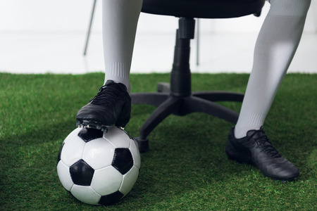 cropped shot of businessman in football boots with soccer ball