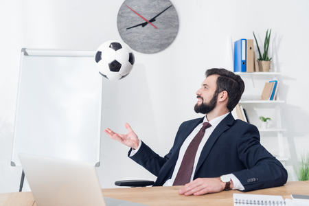 businessman in suit throwing soccer ball at workplace in office Stok Fotoğraf