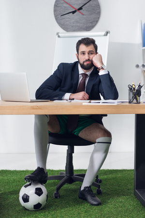 tired businessman with soccer ball sitting at workplace in office Stock Photo