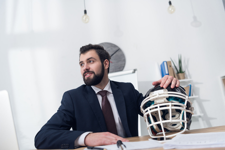 young businessman with rugby helmet at workplace in office
