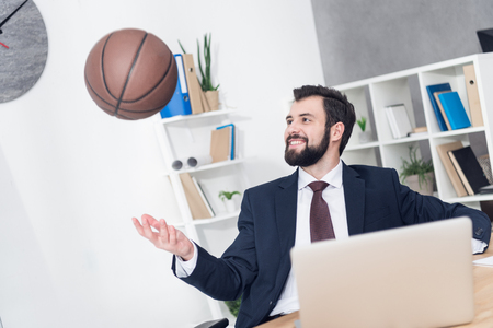 smiling businessman throwing basketball ball at workplace in office