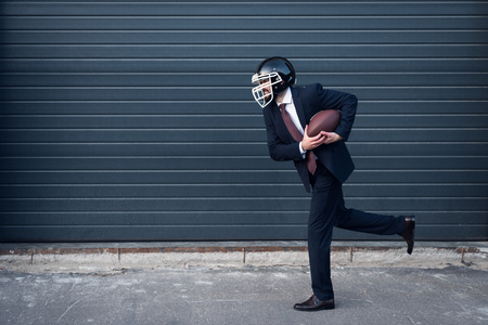 side view of young businessman in suit and rugby helmet with ball in hands running on street