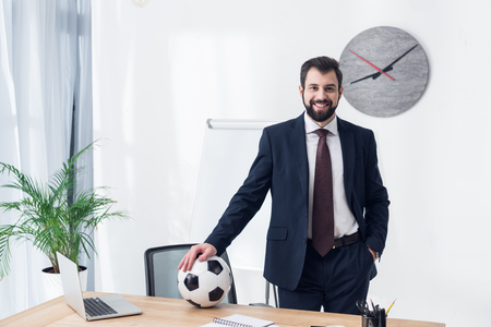 smiling businessman in suit with soccer ball at workplace in office 写真素材