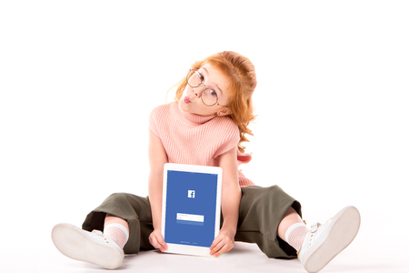 red hair child sitting and holding tablet with loaded facebook page on white Редакционное