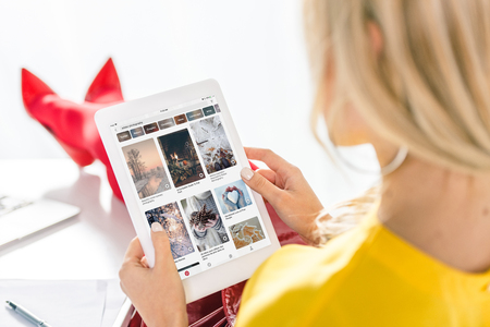 cropped view of woman using digital tablet with pinterest website