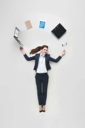 overhead view of businesswoman with various office supplies using laptop isolated on grey