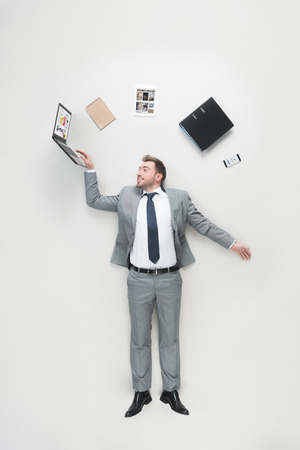 overhead view of businessman with office supplies above head using laptop isolated on grey Editorial