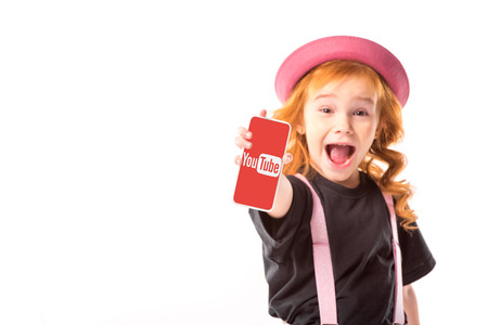 stylish kid in pink hat and suspenders showing smartphone with youtube page isolated on white Redactioneel