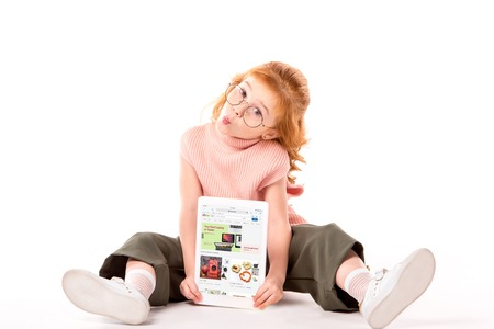 red hair child sitting and holding tablet with loaded ebay page on white Редакционное