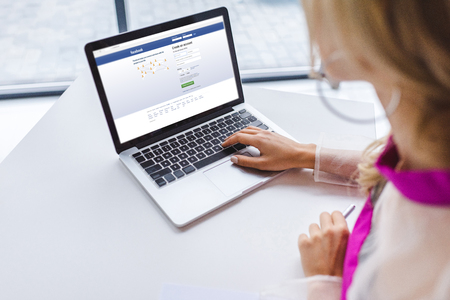 cropped view of woman using laptop with facebook website Stockfoto - 105373521