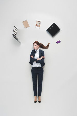 overhead view of businesswoman with various office supplies above head isolated on grey