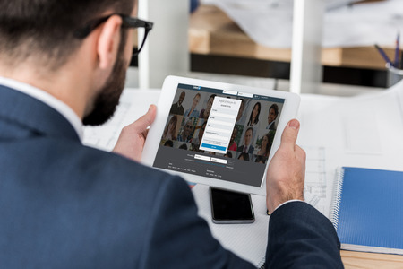 businessman holding tablet with loaded linkedin page