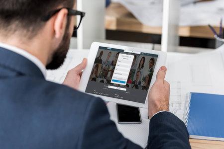 Geschäftsmann hält Tablette mit geladener Linkedin-Seite