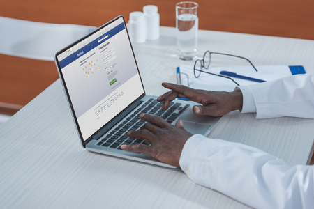 Cropped image of african american doctor sitting with laptop and open Facebook page