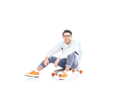 asian teenager with backpack sitting on skateboard isolated on white