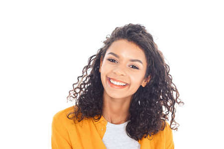 portrait of smiling african american teenager with curly hair isolated on white Stock Photo