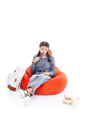 bored teenage student girl studying while sitting on bean bag isolated on white