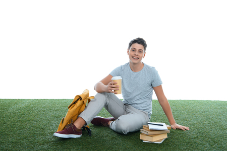 teenage student boy sitting on grass with coffee to go isolated on white