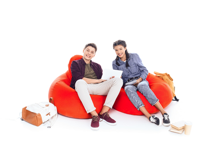 teenage students studying together while sitting on bean bags isolated on white