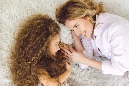 top view of happy mother and adorable curly daughter lying on sheep skin blanket 写真素材