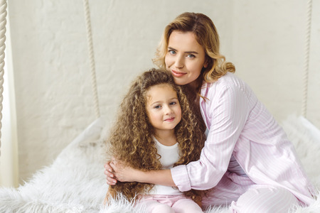 happy mother hugging her adorable curly daughter