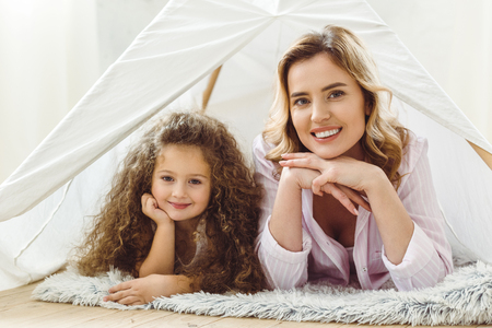 smiling mom and happy curly daughter lying in kid wigwam